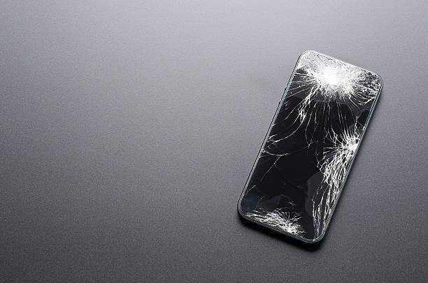 Smartphone with broken screen on dark background - foto de stock