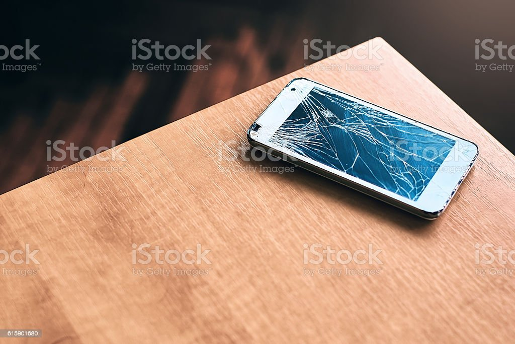 Smartphone with broken screen on the table stock photo