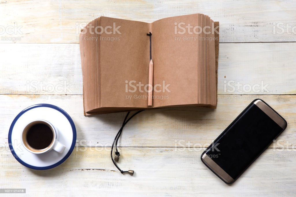 Smartphone with Coffee cup and handmade notebook on wooden table stock photo