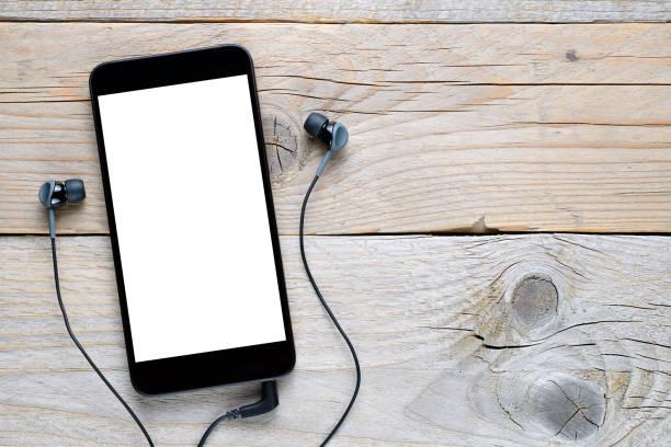 smartphone avec écouteurs sur la table en bois - écouteurs intra auriculaires photos et images de collection