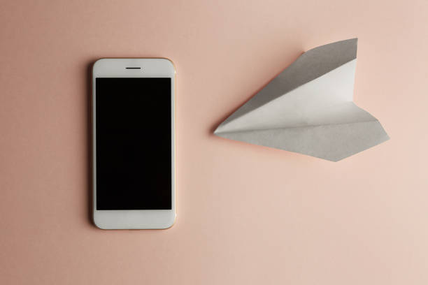 smartphone with flat lay of white paper plane and blank paper on pastel pink color background.concept horizontal. - phone, travelling, copy space imagens e fotografias de stock