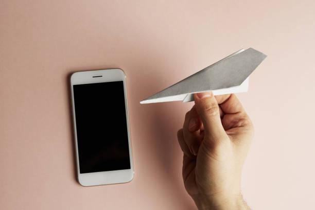 smartphone mit flachen lag der weiße papierflieger in männlicher hand auf pastell rosa farbe hintergrund. konzept-horizontal. - origami mobil stock-fotos und bilder