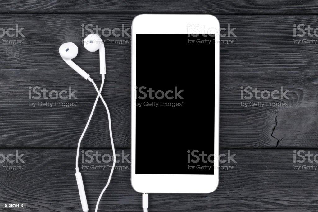 Smartphone mit Kopfhörern auf schwarzer Holztisch. Smartphone mit Solated Bildschirm. Leeren Raum für Text. Kopieren Sie Raum. Smartphone-Bildschirm. Smartphone-mock-up. Kopfhörer. – Foto