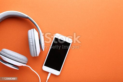 Smartphone with headphones on orange background