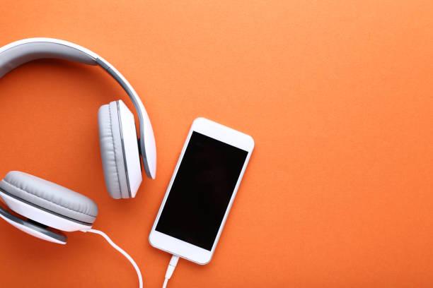 smartphone with headphones on orange background - słuchawka nauszna zdjęcia i obrazy z banku zdjęć
