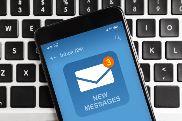 Smartphone With New Email Message Notification On Screen Lying On Laptop Keyboard stock photo