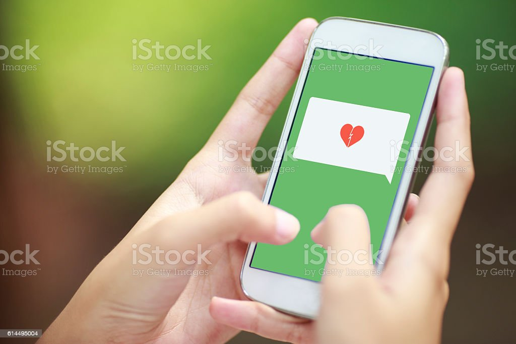 smartphone with speech bubble and broken heart - foto de acervo