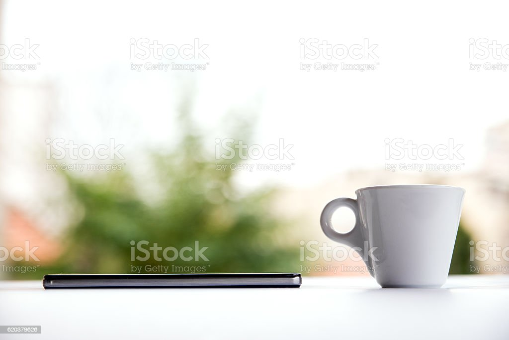 Smartphone with white cup of coffee on the white table zbiór zdjęć royalty-free
