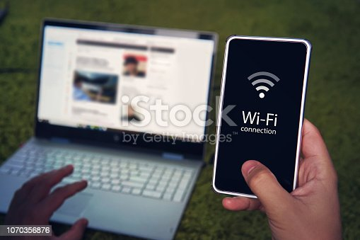 Smartphone with wifi connection generic icon on the screen hold by man on the background of laptop display and keyboard. Man uses Wi-Fi hot spot to get to domestic internet access. Wireless gadgets.