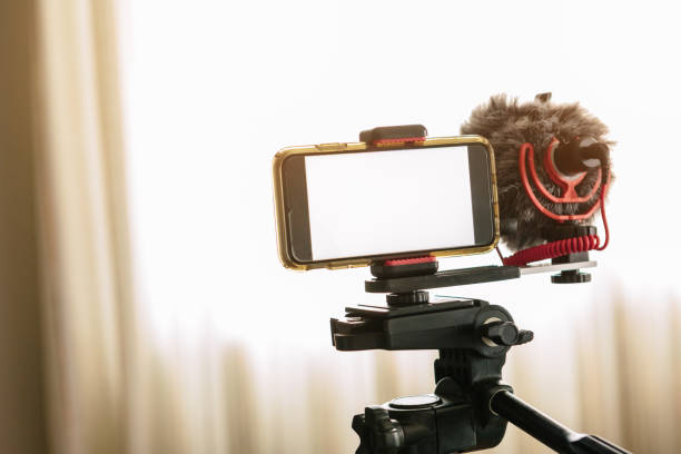 smartphones connected to an external microphone and coupled to a tripod.