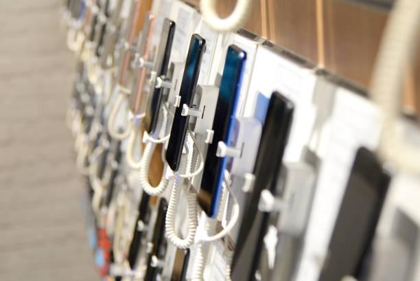 smartphones an der theke eines elektronikhauses - freizeitelektronik stock-fotos und bilder