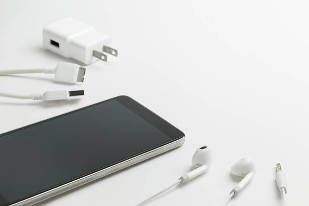 smartfony z słuchawki i ładowarki - akcesorium osobiste zdjęcia i obrazy z banku zdjęć