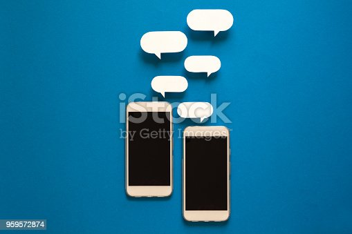 istock Smartphones with paper speech bubbles on blue background. Communication concept. 959572874