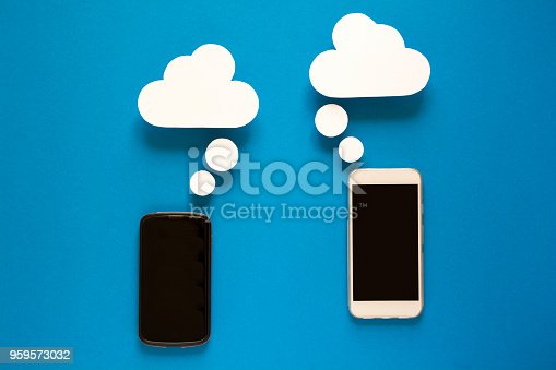 istock Smartphones with paper speech bubbles on blue background. Communication concept. 959573032