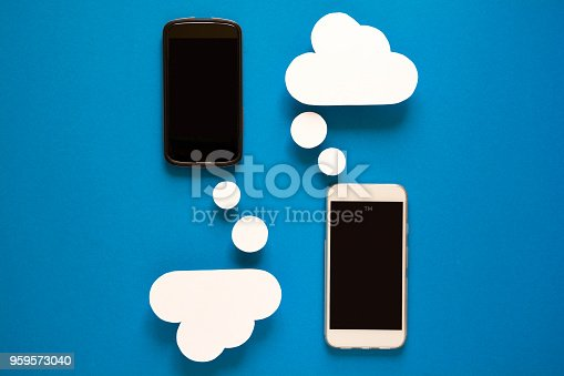 istock Smartphones with paper speech bubbles on blue background. Communication concept. 959573040