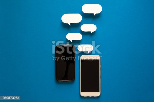 istock Smartphones with paper speech bubbles on blue background. Communication concept. 959573284