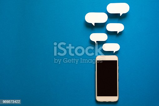 istock Smartphones with paper speech bubbles on blue background. Communication concept. 959573422
