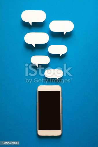 istock Smartphones with paper speech bubbles on blue background. Communication concept. 959575500
