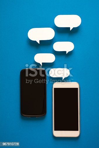 istock Smartphones with paper speech bubbles on blue background. Communication concept. Top view. Copy space. Paper composition. 967910728