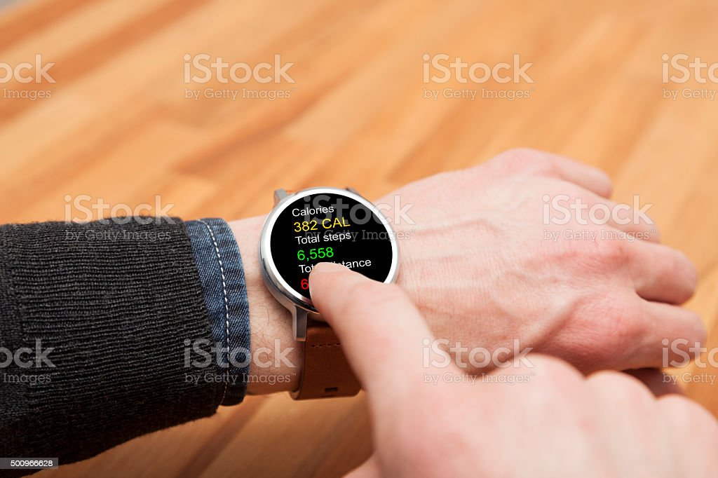Smart watch on wrist displaying steps, calories and distance on...