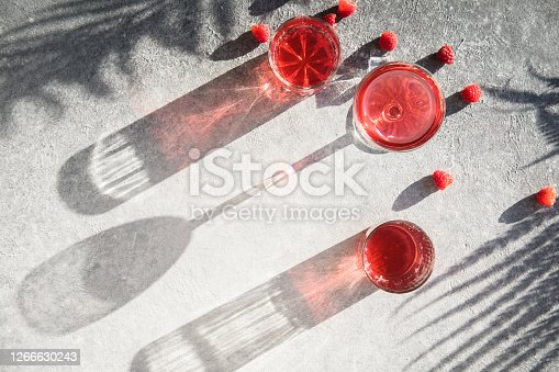 Smash gin alcoholic cocktail. Long raspberry drink on  gray stone background, copy space. Sunlight through a glass of bevarage. Sun hard light shadow reflection