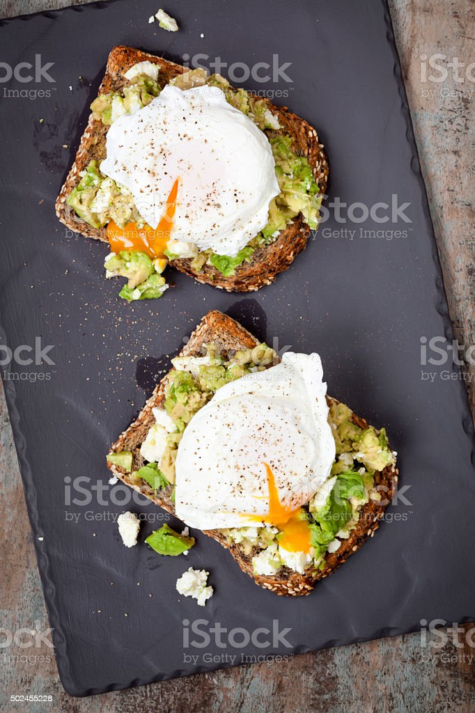 Smashed Avocado and Feta Toast with Poached Eggs stock photo