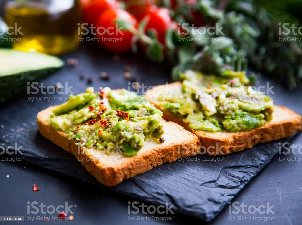 Smashed avocado on toast, tasty healthy appetizers with cherry tomatoes and herbs, olive oil stock photo