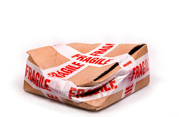 A smashed box with fragile tape all around it stock photo