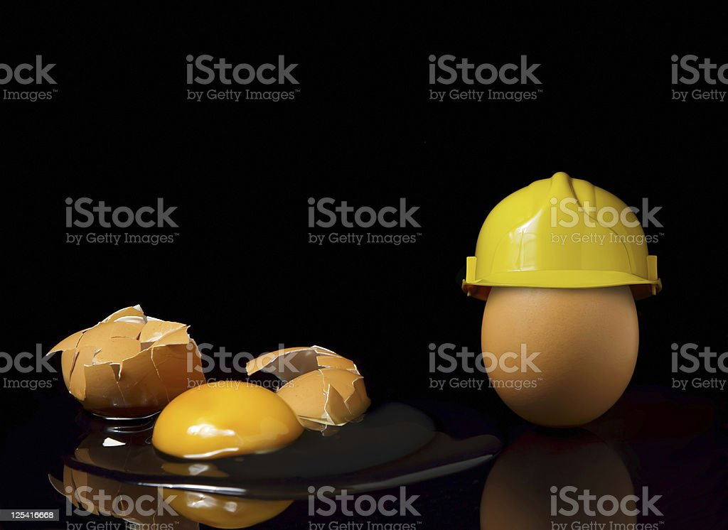 Smashed egg and an egg wearing a safety hat royalty-free stock photo