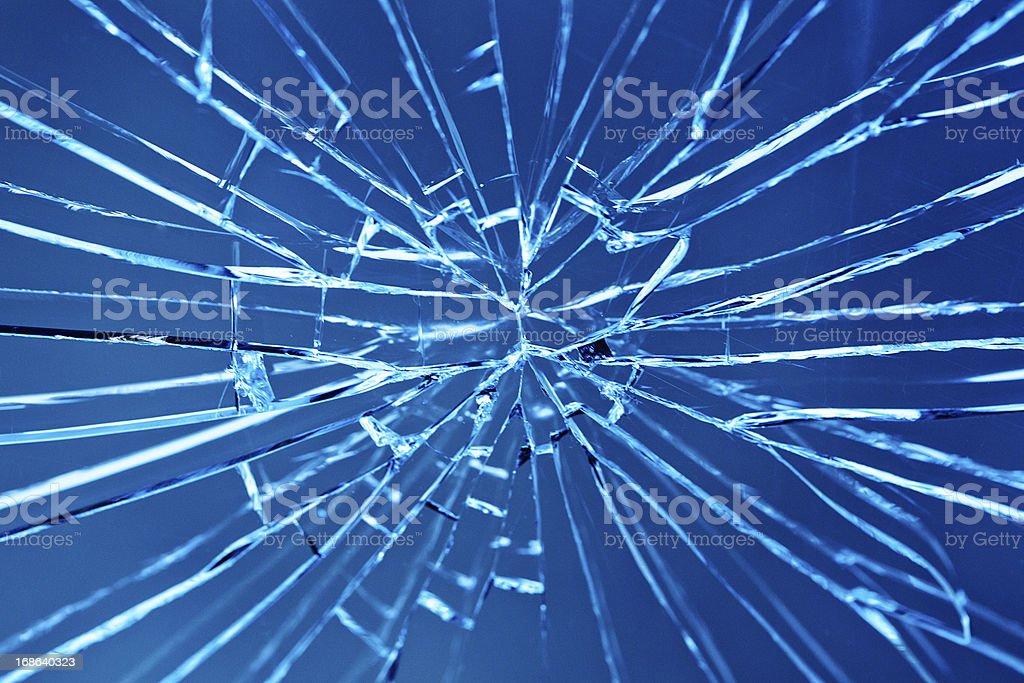 Smashed window with multiple cracks against blue background royalty-free stock photo