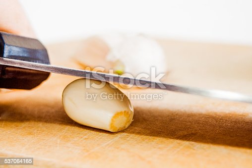 Smashing fresh tasty organic garlic on an old wooden plank with knife. Shallow depth of field.