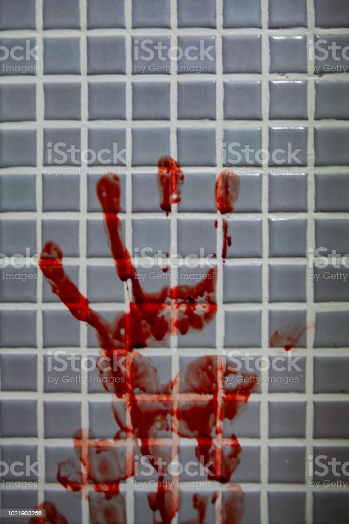 Smeared fresh bloody handprint or bloodstains with streaks on bathroom tiles wall. stock photo