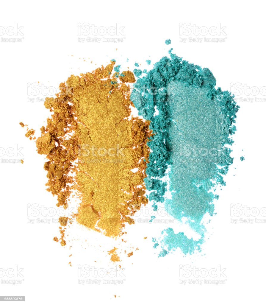 Smears of crushed teal and golden shiny eyeshadow royalty-free stock photo
