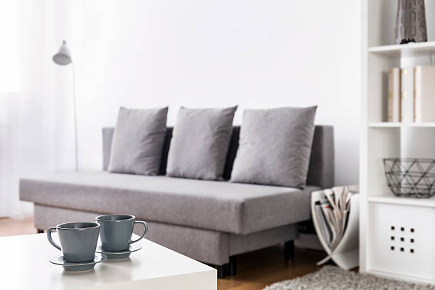 Smell of coffee is all around the place Close-up of two grey coffee cups on a white coffee table with blurred living room in the background magazine rack stock pictures, royalty-free photos & images