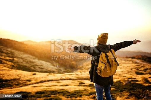 Rear view of hipster woman on the top of the hill with outstretched arms looking at view