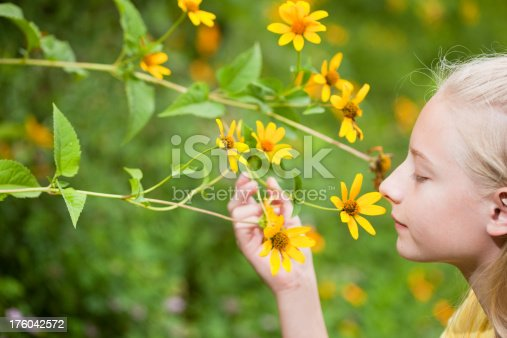 Close up of a teen girl holding and smelling a flower.