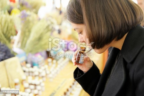 A young woman smells lavender essential oil from a bottle. Taken at the Provencal Market, le Petit Marche Provencal, Antibes, France.