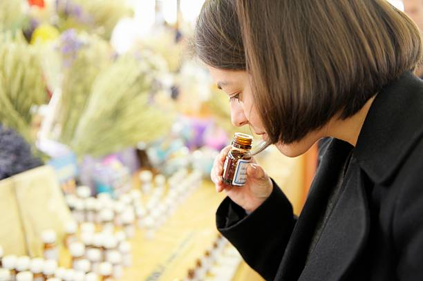 smelling essential oils on a market stall - aromatherapy stock photos and pictures