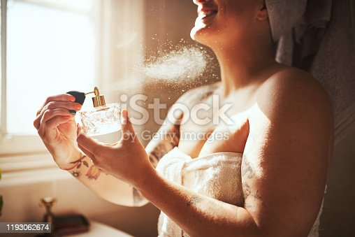 Cropped shot of a young woman spraying perfume during her morning beauty routine