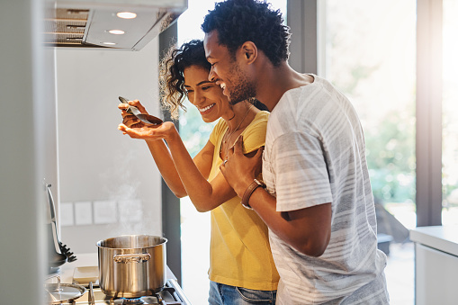Cropped shot of a young married couple tasting the food they are making in the kitchen at home