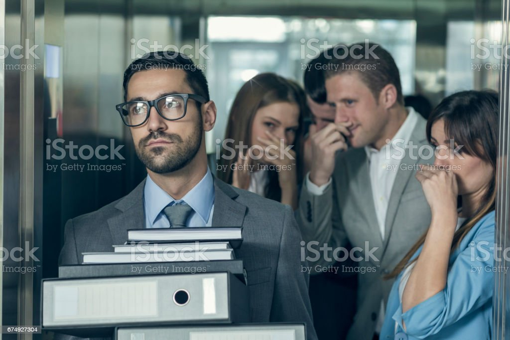 Smelly businessman affecting his coworkers in an elevator stock photo