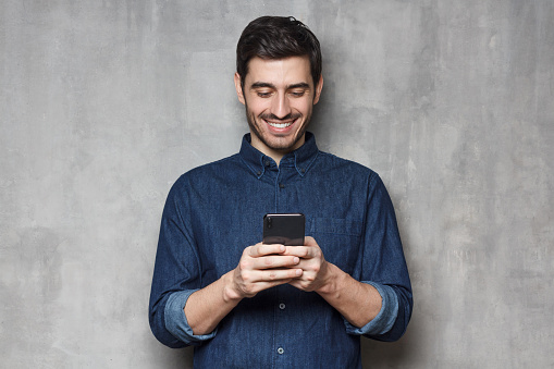 825083556 istock photo Smiiling business man in denim shirt and trendy eyeglasses standing against gray textured wall, typing a message using his phone 1166255867
