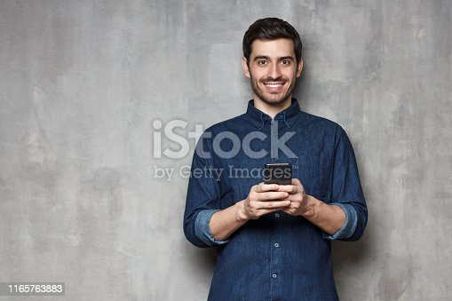 825083556istockphoto Smiiling modern business man  standing against gray textured wall, holding his phone with both hands. Copy space on the left side 1165763883