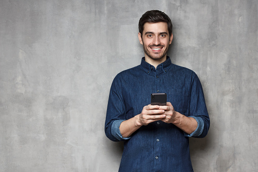 825083556 istock photo Smiiling modern business man  standing against gray textured wall, holding his phone with both hands. Copy space on the left side 1165763883