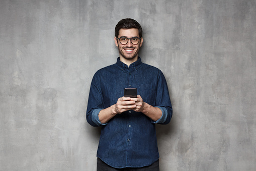 825083556 istock photo Smiiling modern businessman in denim shirt and trendy eyeglasses standing against gray textured wall, holding his phone with both hands 1164586398
