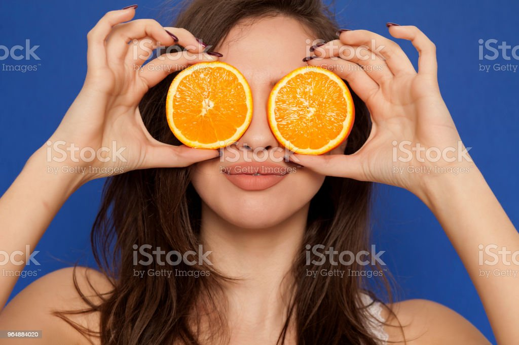 Smiing young woman posing with slices of oranges on her face on blue background royalty-free stock photo