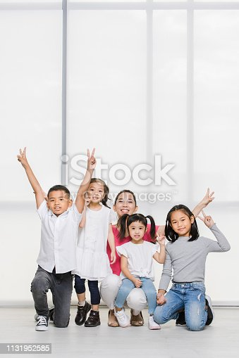 istock Smile Asian woman in pink shirt and Asian boy and girls squat on floor together, big white window behind them. 1131952585