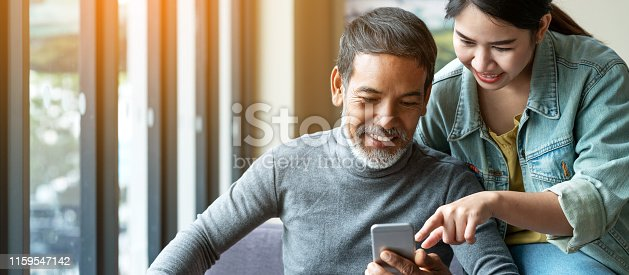 istock Smile attractive stylish short beard mature asian man using smartphone with young woman. Daughter teach asian old man or dad using internet social media network technology with digital gadget at home. 1159547142