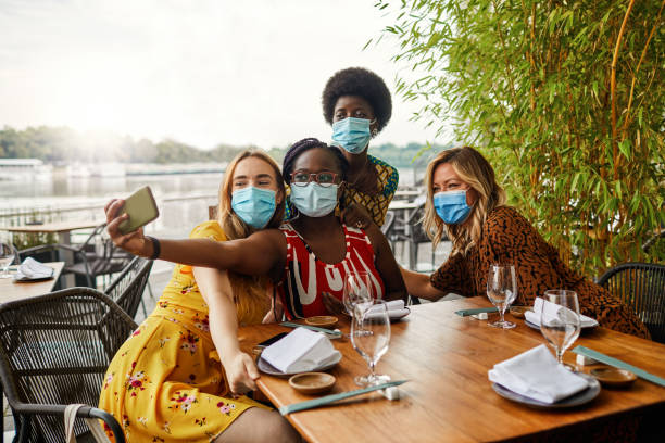Smile Behind The Face Masks - New Normal Friendship Concept stock photo