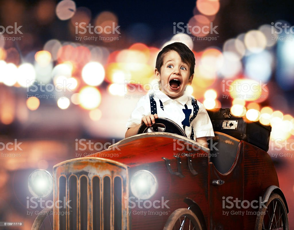 Smile child in wooden car night on street stock photo